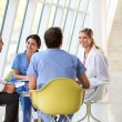 Stockfoto: Medical Team Meeting Around Table In Modern Hospital