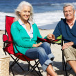 Royalty-Free Stock Photo: Senior Couple Sitting On Beach In Deckchairs Having Picnic