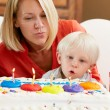 Family Celebrating Children's Birthday With Grandmother - Stock Photo