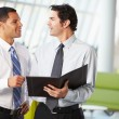 Two Businessmen Having Informal Meeting In Modern Office - Foto Stock