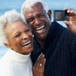 Senior Couple With Camera On Beach — Stock Photo