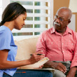 Nurse Discussing Records With Senior Female Patient During Home — Stock Photo