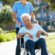 Stock Photo: Carer Pushing Unhappy Senior WomIn Wheelchair