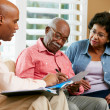 Financial Advisor Talking To Senior Couple At Home — Stockfoto