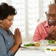 Senior Couple Saying Grace Before Meal At Home - Foto Stock