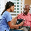 Foto Stock: Nurse Visiting Senior Male Patient At Home