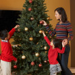 Mother And Children Decorating Christmas Tree — Stock Photo