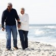 Senior Couple Walking Along Beach Together — Stock Photo #24651361
