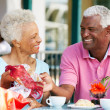 Senior Couple Enjoying Snack At Outdoor Cafe After Shopping — Stock Photo #24651507
