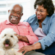 Happy Senior Couple Sitting On Sofa With Dog — Stock Photo