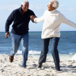 Stock Photo: Romantic Senior Couple Running Along Beach