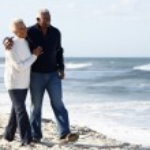 Senior Couple Walking Along Beach Together — Stock Photo #24652403