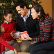 Family Opening Presents In Front Of Christmas Tree — Stockfoto