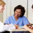 Doctor And Nurses In Discussion At Nurses Station — Stock Photo #24652783