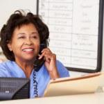 Nurse Making Phone Call At Nurses Station — Stock Photo #24652787