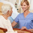 Nurse Taking To Senior Female Patient Seated In Chair By Hospita - Foto Stock