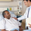 Doctor Visiting Senior Male Patient On Ward — ストック写真