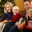 Stockfoto: Family Opening Presents In Front Of Christmas Tree