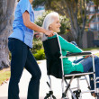 Carer Pushing Senior Woman In Wheelchair — Stock Photo