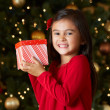 Girl Holding Christmas Present In Front Of Tree - Foto Stock
