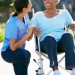 Stockfoto: Carer Pushing Senior WomIn Wheelchair