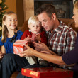 Family Opening Presents In Front Of Christmas Tree — Stock Photo #24653843