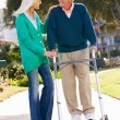 Stock Photo: Senior WomHelping Husband With Walking Frame