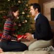 Couple Opening Presents In Front Of Christmas Tree — Stock Photo