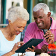 Stock Photo: Senior Couple Using Tablet Computer At Outdoor Cafe