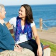 Senior Man Sitting On Bench With Adult Daughter By Sea — Stock Photo