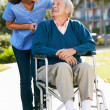 Carer Pushing Senior Man In Wheelchair — Stock Photo #24654175