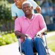 Senior Woman Pushing Husband In Wheelchair - Stock Photo