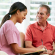 Stock Photo: Nurse Discussing Records With Senior Male Patient During Home Vi