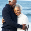 Romantic Senior Couple Hugging On Beach - Stock Photo