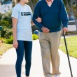 Teenage Volunteer Helping Senior Man Walking Through Park — Stock Photo #24654555