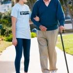 Teenage Volunteer Helping Senior Man Walking Through Park — Stock Photo