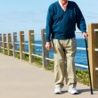 Senior Man Walking Along Path By The Sea — Stock Photo #24654627