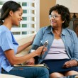 Nurse Visiting Senior Female Patient At Home - Foto Stock