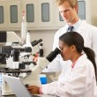 Male And Female Scientists Using Microscopes In Laboratory — Stock Photo