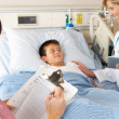 Doctor Using Digital Notepad Whilst Visiting Child Patient - Foto Stock