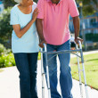 Senior Woman Helping Husband With Walking Frame - Stock Photo