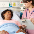 Nurse Visiting Senior Female Patient On Ward - Stock Photo