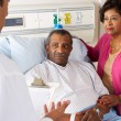 Doctor Talking To Senior Couple On Ward — Foto Stock #24655313