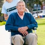 Teenage Volunteer Pushing Senior Man In Wheelchair — Stock Photo