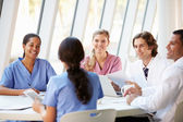 Medical Team Meeting Around Table In Modern Hospital — Stockfoto