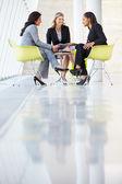Tre imprenditrici incontro intorno a tavolo in ufficio moderno — Foto Stock