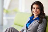 Portrait Of Businesswoman Sitting On Sofa In Modern Office — Stock Photo