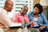 Financial Advisor Talking To Senior Couple At Home — 图库照片