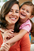 母亲和女儿在家里的沙发上坐的肖像 — 图库照片