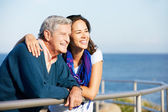 Senior Man With Adult Daughter Looking Over Railing At Sea — Stock fotografie